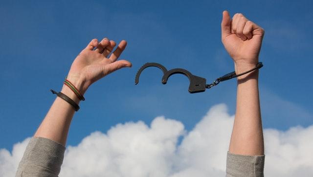 des mains et une paire de menottes pour illustrer la prise en charge des dépendances dans notre cabinet de psychologue à villeneuve d'ascq, dans la métropole de lille